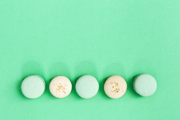 甘いマカロンからの列は、おいしいとさまざまな色の盛り合わせ。カラートレンドミントの丸いビスケット。甘い食べ物と健康への害。