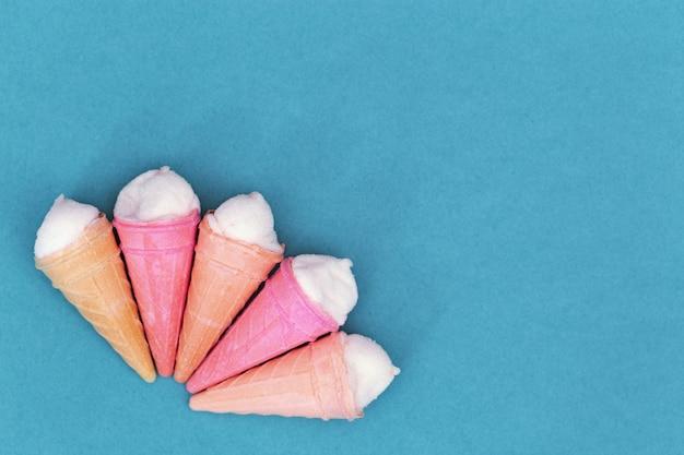Малые вафельные рожки с мороженым на голубой бумаге с копией пространства.