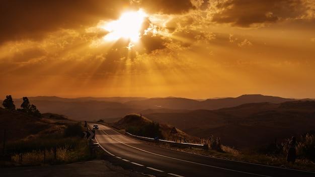 空の夕日の美しい自然の冬の道。太陽の光。雲と夕方の空。風光明媚な道路や車の旅。旅行の概念。車の旅行の冒険。