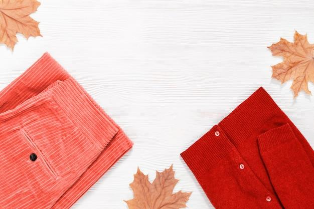 Осенняя квартира лежала с теплой женской одеждой. розовые вельветовые брюки и красный пуловер. женские аксессуары модного цвета. вид сверху.
