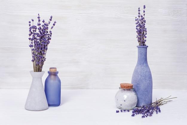 Концепция естественного здравоохранения. фиолетовая лаванда и морская соль для тела. бутылки с лавандой на деревянных фоне.
