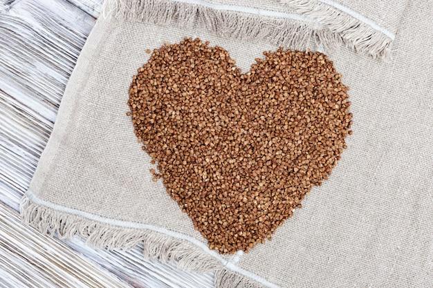 ハートの形で食欲をそそるそば。コピースペースを持つ木製の背景にソバの種子。健康的な食事。素朴なスタイル。