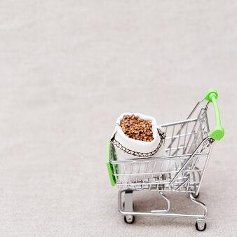 コピースペースと明るい背景にそばの完全袋袋とショッピングカート。健康食品。天然有機穀物。