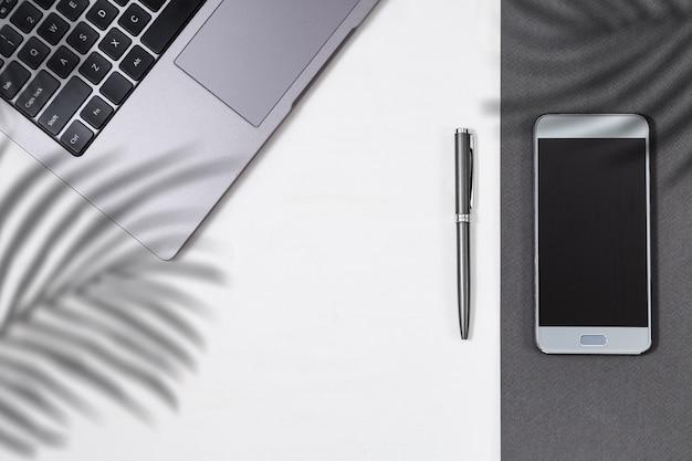 Современная концепция образования, рабочее место для студента. рабочее пространство с тенью пальмовых листьев. серый компьютер, ручка и смартфон на столе. вид сверху. квартира лежала. копировать пространство
