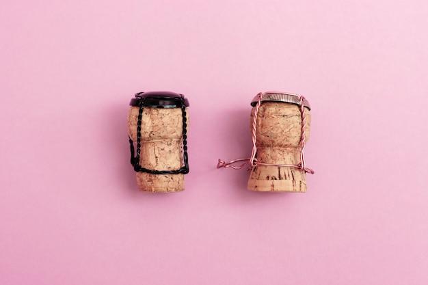 Девочка и мальчик персонажей из шампанского пробки и мюзиклы вместе на розовом фоне цветов. концепция на день святого валентина на тему отношений между мужчиной и женщиной.