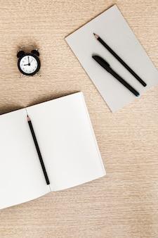 学校のノートと鉛筆、ペン、軽い木製の机の上のノートのステッカーを開きます。学校のコンセプトに戻る。在宅勤務。上からの眺め。