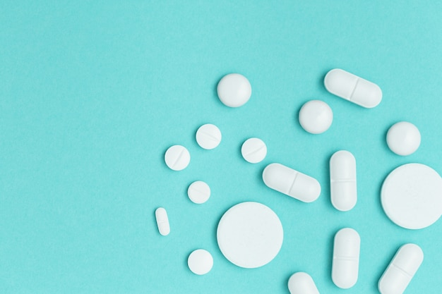 青い背景の上の各種医薬品錠剤、錠剤、カプセル。健康管理。医療の背景。上面図。コピースペース