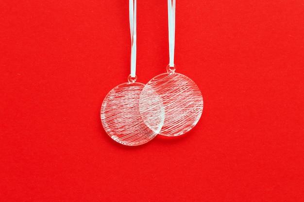 Новогодние стеклянные шарики с простым белым узором, висящие на красной поверхности