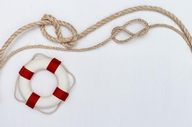 Плоская прокладка веревки с морским узлом и спасательным кругом.