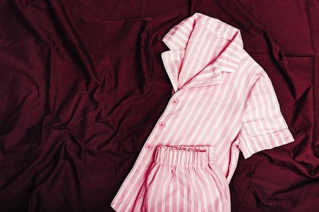 Розовая пижама для женщины на темно-бордовом простыне на кровати