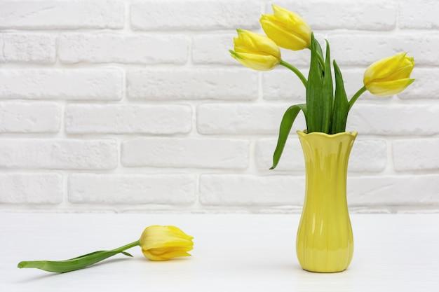 小さなセラミック花瓶の黄色いチューリップの花の花束