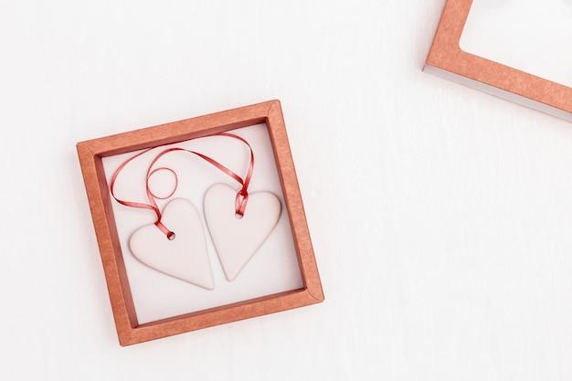 Два белых сердца вместе в бумажной коробке
