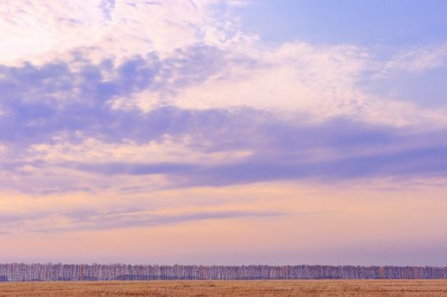 青とピンクのパステルカラーの夕日と雲の空の背景。最小限のスタイルで秋の風景。