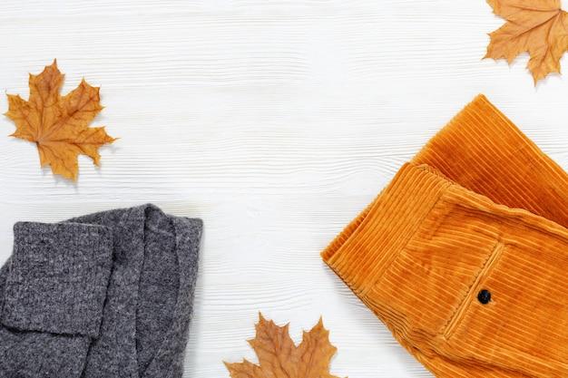 秋の暖かい服。トレンディなコーデュロイオレンジパンツとコピースペースを持つ白い木製の背景に灰色のウールのセーター。女性の服。ファッションのコンセプトです。