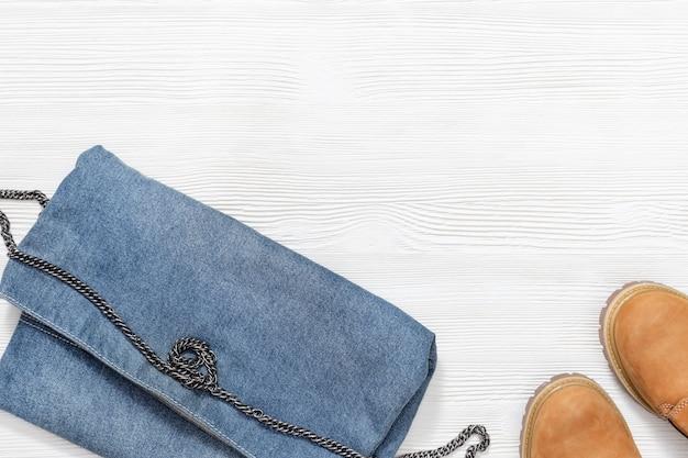 コピースペースを持つ白い木製の背景にトレンディなオレンジ色の靴とデニムのハンドバッグ。女性のカジュアルウェア。ファッションのコンセプトです。フラット横たわっていた。上面図。