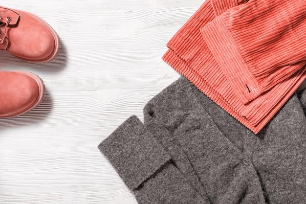 寒い季節でも快適な暖かい服装。明るいコーデュロイのズボンはグレーのプルオーバーと快適な靴を編みました。女性のアクセサリーのトレンドカラー。上面図。フラット横たわっていた。
