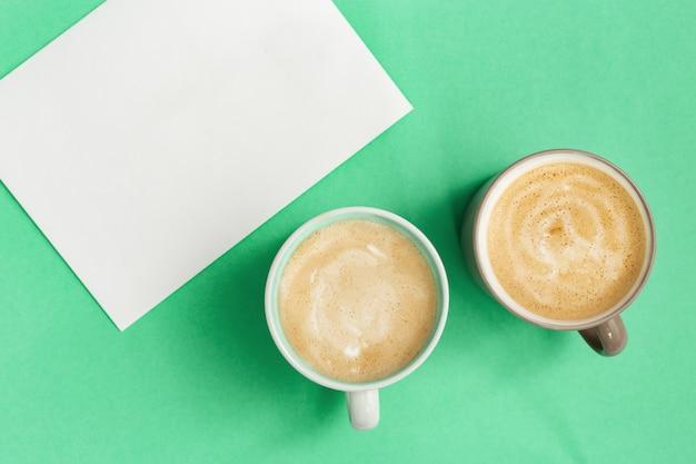 Закройте две чашки кофе капучино и чистый лист бумаги для написания идей. время для отдыха и размышлений. вид сверху и плоская планировка на мятном фоне.