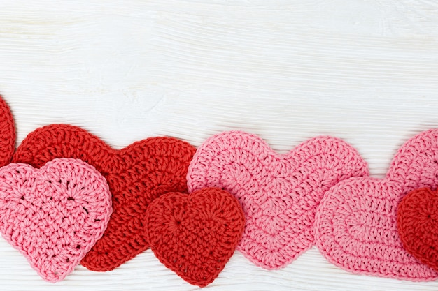 ロマンスのコンセプトが大好きです。自然な木の表面に赤とピンクのハートのフレーム。バレンタインデーの背景