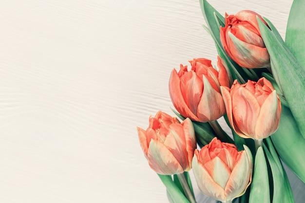 オレンジと黄色のチューリップの花束。テキストまたはお祝いのコピースペースと明るい休日の背景。春のグリーティングカード。