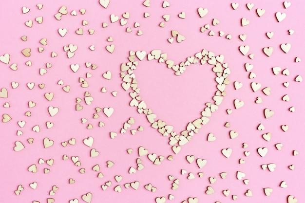 ピンクの紙に大小のハート。誕生日の休日の背景