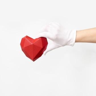 白い背景の白い繊維の手袋を手に体積の紙のハート。ヘルスケアと医療の概念。