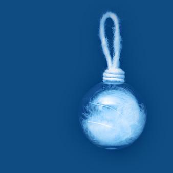 古典的な青い紙の背景に白い羽でクリスマスボール。伝統的な休日の冬のおもちゃがぶら下がっています。最小限のクリスマスコンセプト。