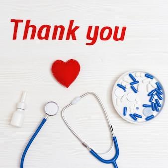 コピースペースと白い木製の背景に医療聴診器、薬とテキスト「ありがとう」とフラットレイアウト。医療関係者への感謝の言葉。