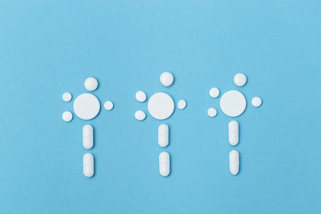薬の薬、青い背景に花の形の錠剤。楽観主義とヘルスケア。医学的背景として期待しています。