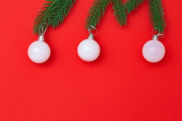 Елочная игрушка на зеленых еловых ветках, три белых стеклянных шарика крупным планом на красном