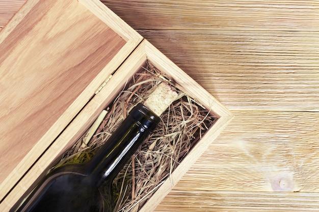 古い木製の背景の木の箱に赤ワインのガラス瓶