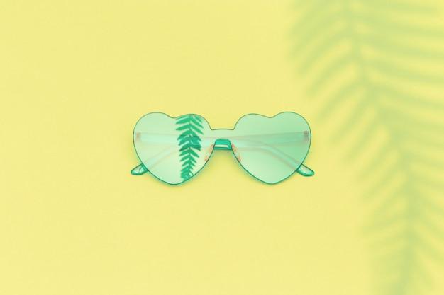 Стильные очки в форме сердца с тенью пальмовых листьев на желтом фоне с копией пространства. красивые модные зеленые солнцезащитные очки.