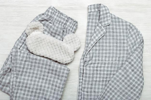 グレーのパジャマとふわふわの睡眠マスク
