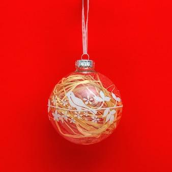 塗られた鳥と赤い紙の背景の中の天然素材で透明な新年のガラス玉。創造的な休日のクリスマスコンセプト。