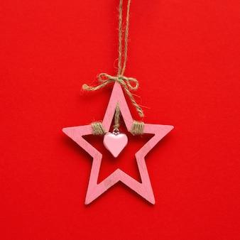 木製のクリスマスの星、正月飾り。天然素材。赤い紙の背景にピンクのホリデースター。
