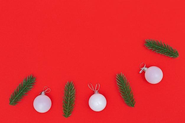 新年の白いホリデーボールとモミの木の小枝。はがきや招待状のコピースペースとクリスマスの装飾。クリスマスのための創造的な最小限のお祝いのコンセプト。