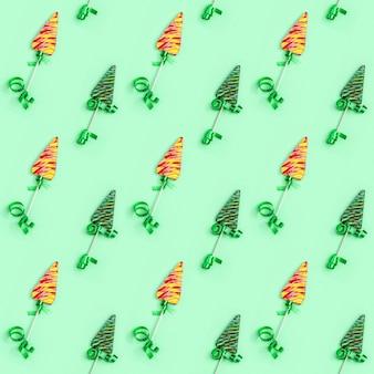 新年やクリスマスの色キャンディ創造的なシームレスパターン。緑の背景にクリスマスツリーのような形をしたロリポップ。
