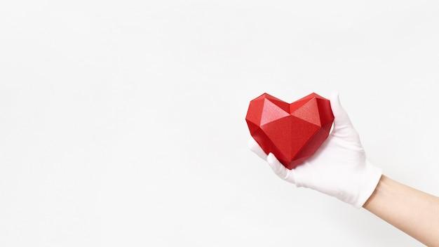 Объемное бумажное сердце в руке с белой текстильной перчаткой на белом