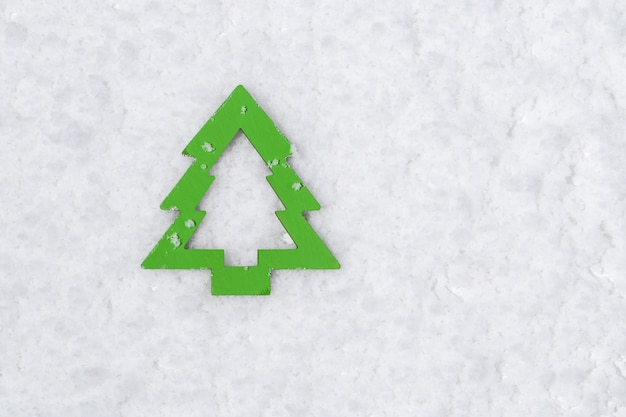 雪の表面に木製の緑のクリスマスツリーのシンボル