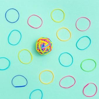 平らな面にある色とりどりの薄いゴムバンドのボール