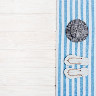 Полотенце, соломенная шляпа и пляжные тапочки