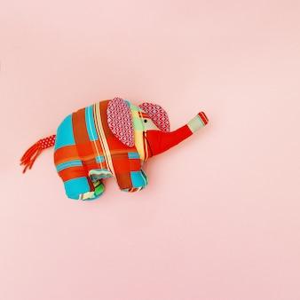 ピンクのパステル表面に明るい子供たちの柔らかいおもちゃの象