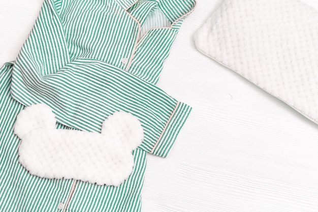 女の子のためのパジャマ、寝るためのアイマスク、白い木の柔らかいふわふわのクッション。