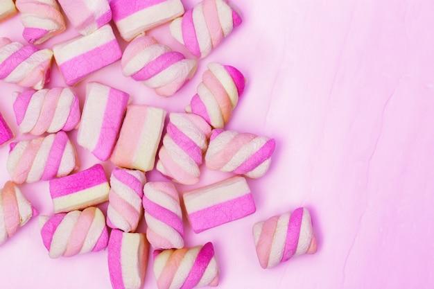 甘い小さなマシュマロからピンクの背景。