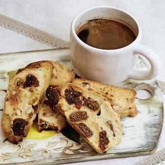 木の板にコーヒーカップとクッキービスコッティ。