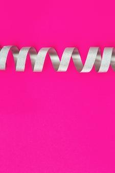 ピンクの紙の上の銀のスパイラルリボン。