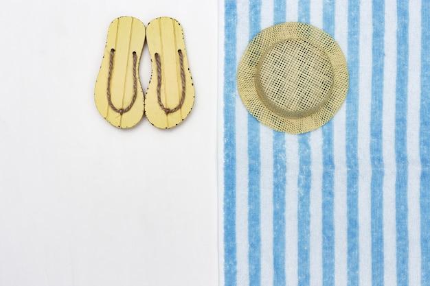 夏の靴、帽子、テリータオル。ビーチアクセサリー。夏の背景。最小限のスタイル。コピースペース。