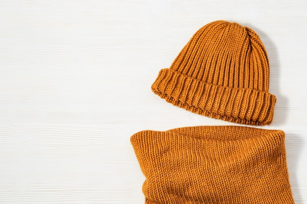 ファッショナブルなニット服明るいオレンジ色、暖かい帽子、白い木の居心地の良い柔らかいスカーフスヌード