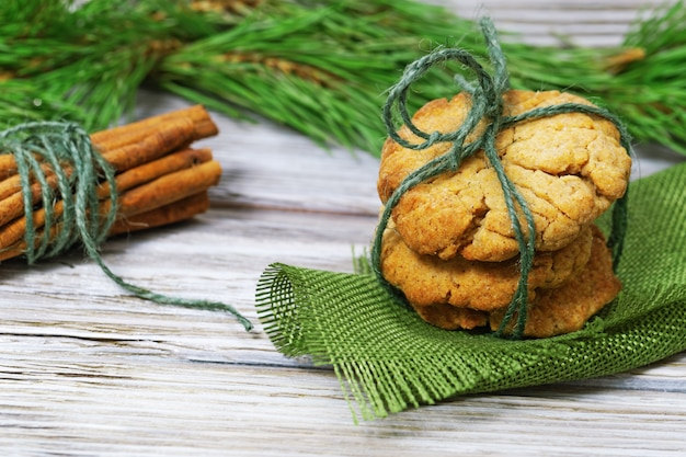 木の松の枝で飾られたジンジャーブレッドクッキーとシナモンの棒の山