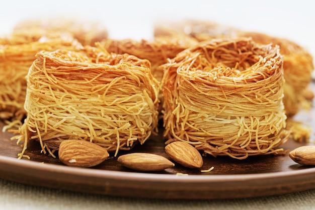 蜂蜜とナッツの伝統的な東洋の甘い鳥の巣をクローズアップ。