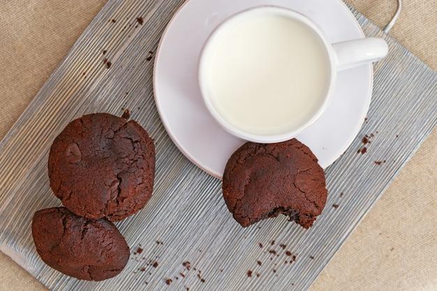 木製の机の上のミルクとチョコレートクッキー。